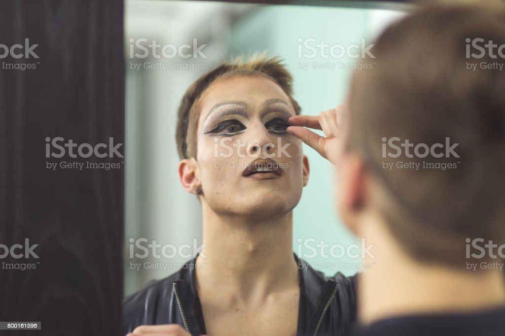 Man gets dressed in drag attire in bathroom stock photo