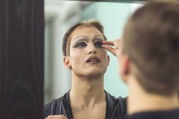 man gets dressed in drag attire in bathroom - transvestite stock photos and pictures