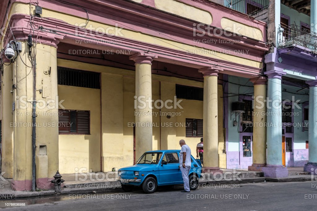 Man gets in an old car outside a classic building in Havana stock photo