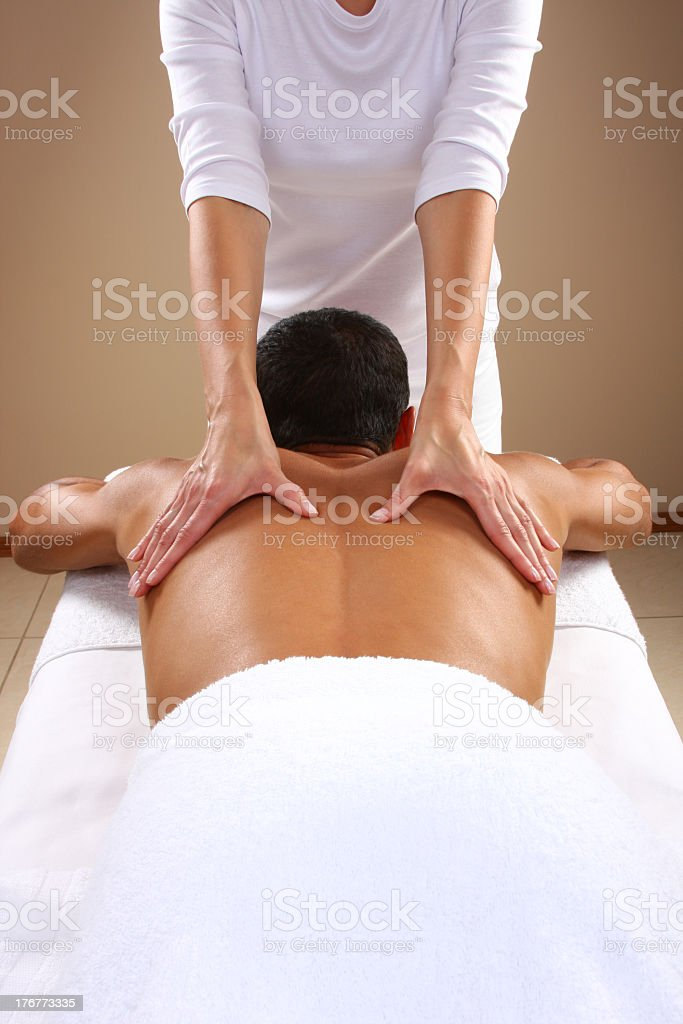 Man getting a back massage by a female masseuse stock photo