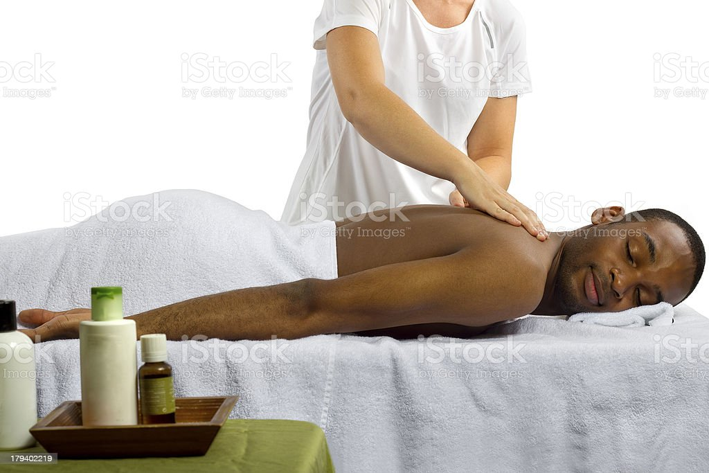 Man Getting a Massage from a Masseuse with Spa Products stock photo