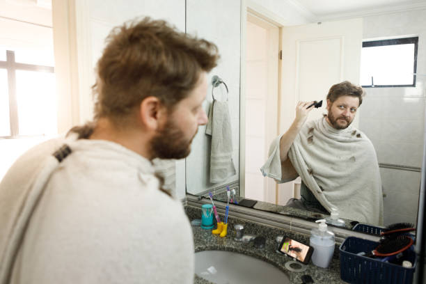 Man getting a self haircut at home. stock photo