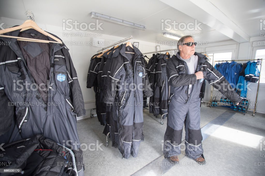 Man getting dressed for tour of Langjokull Glacier in Iceland. stock photo