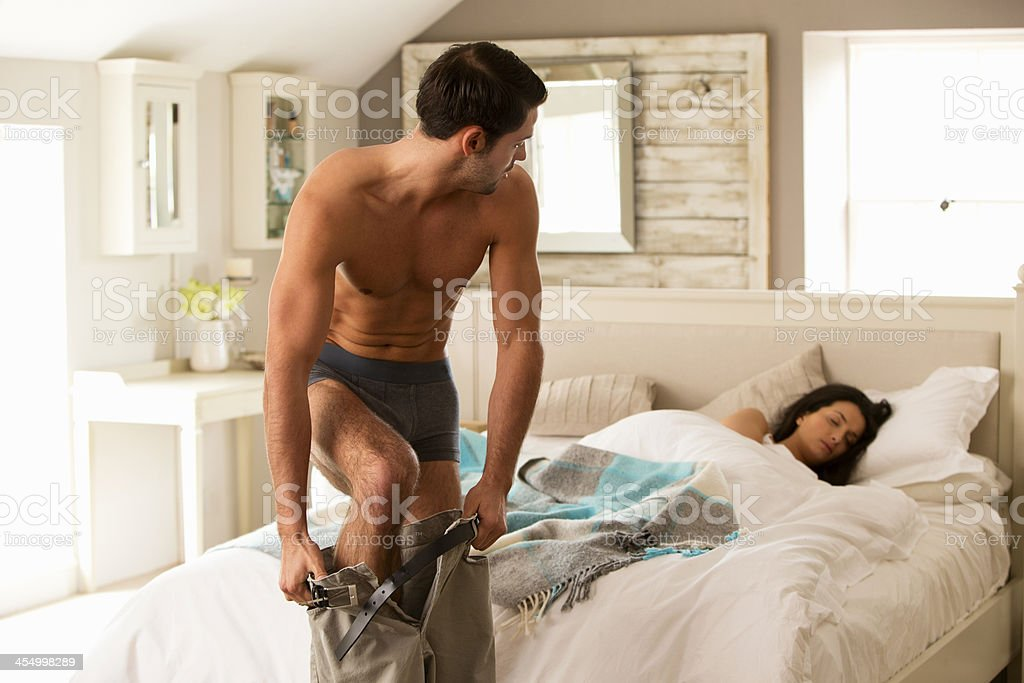 Man getting dressed next to sleeping woman stock photo