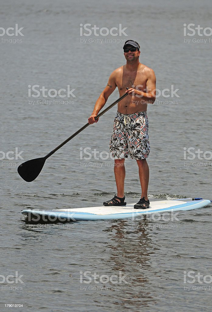 Man getting exercise by paddleboarding stock photo