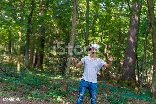 Happy man getting experience using VR-headset glasses of virtual reality in forest