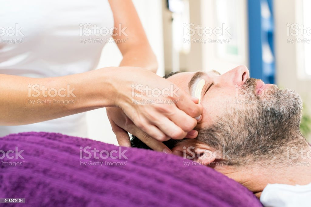 Man getting eyebrows waxed stock photo