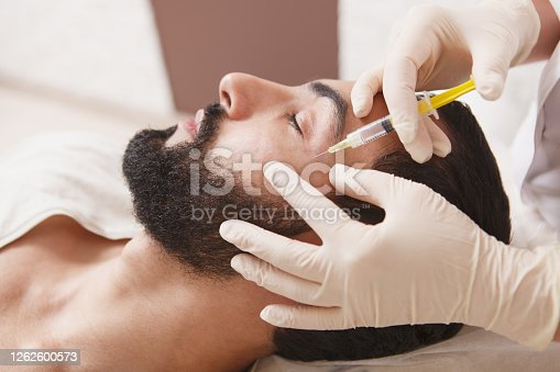 Bearded man getting anti-wrinkle face filler treatment by beautician