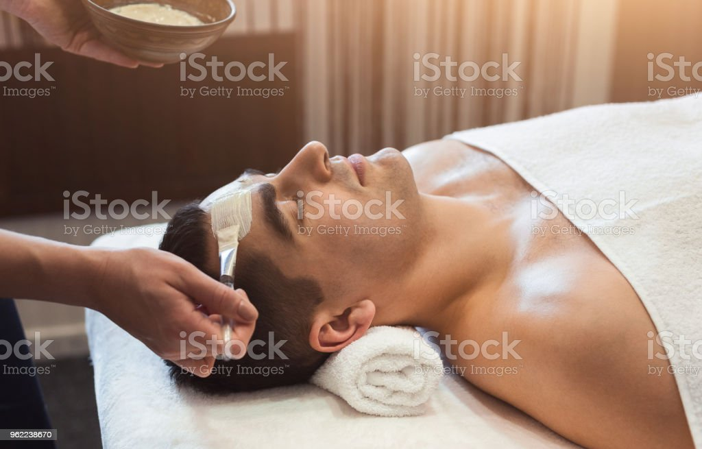 Man getting face mask by beautician at spa stock photo