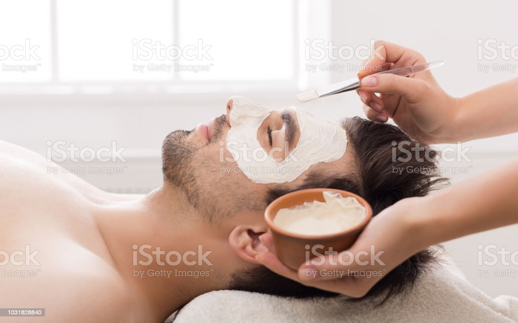 Man getting facial nourishing mask at spa salon stock photo