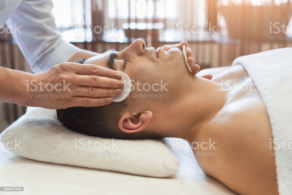 Man getting facial treatment at beauty salon royalty-free stock photo