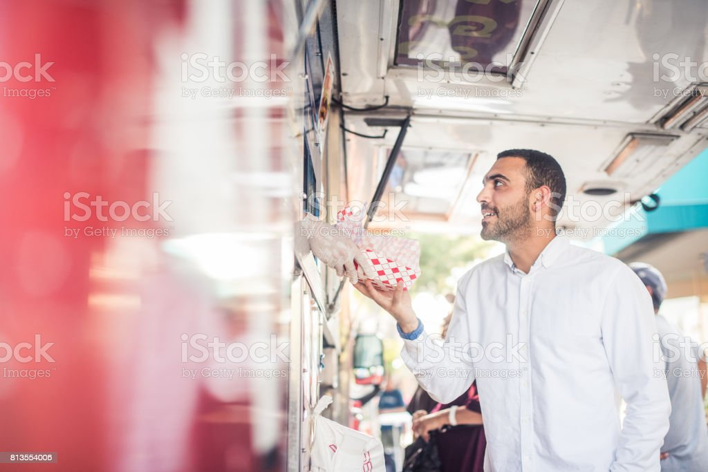 Man Getting Food at the Pick Up Window of Food Truck stock photo