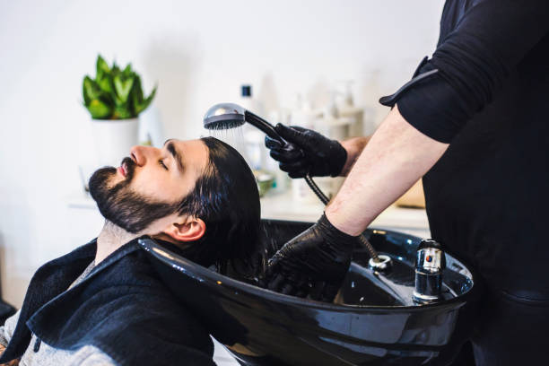 Man getting hair washed at hairdresser stock photo