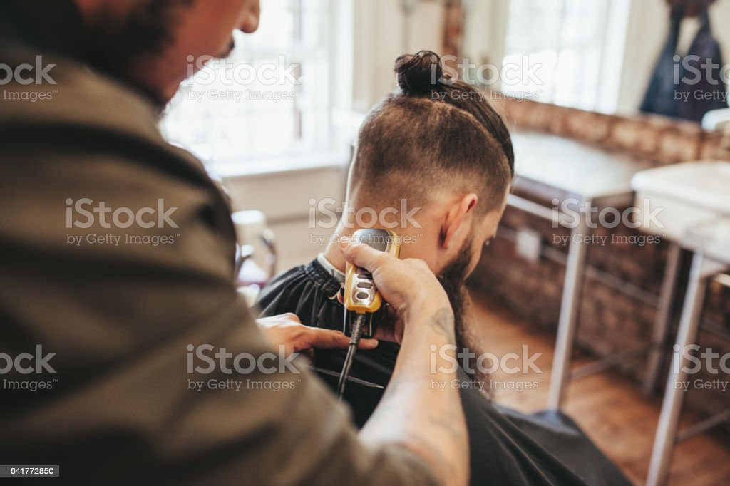 Man getting haircut by barber at salon stock photo
