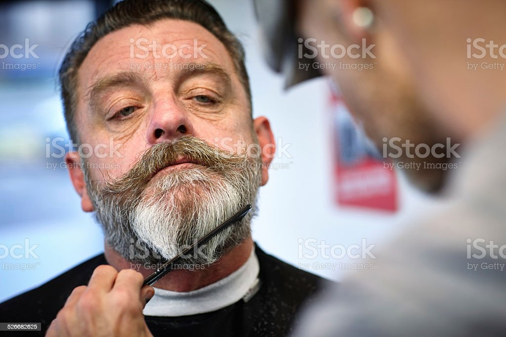 Man getting his beard trimmed stock photo