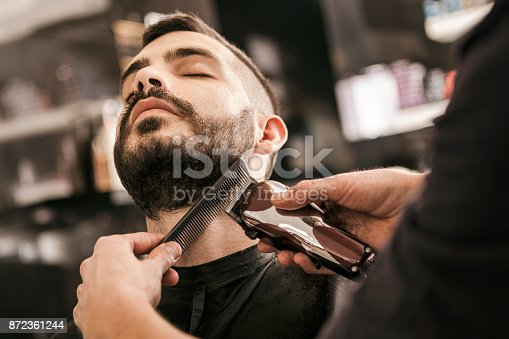 istock Man getting his beard trimmed with electric razor 872361244