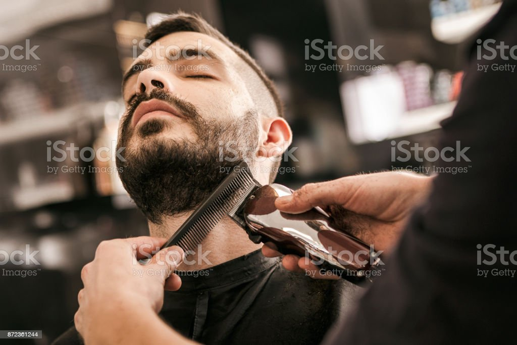 Man getting his beard trimmed with electric razor - fotografia de stock
