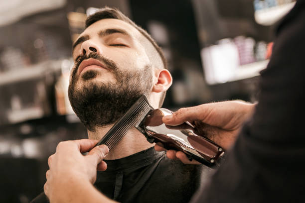Man getting his beard trimmed with electric razor stock photo