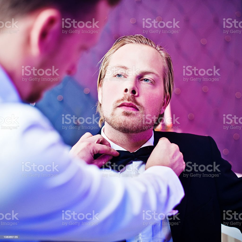 Man getting his bow tie fixed royalty-free stock photo