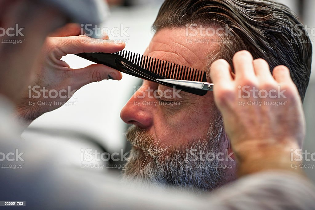 Man getting his eyebrows trimmed at barber shop stock photo