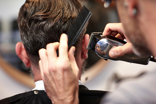Man getting his hair cut at salon stock photo