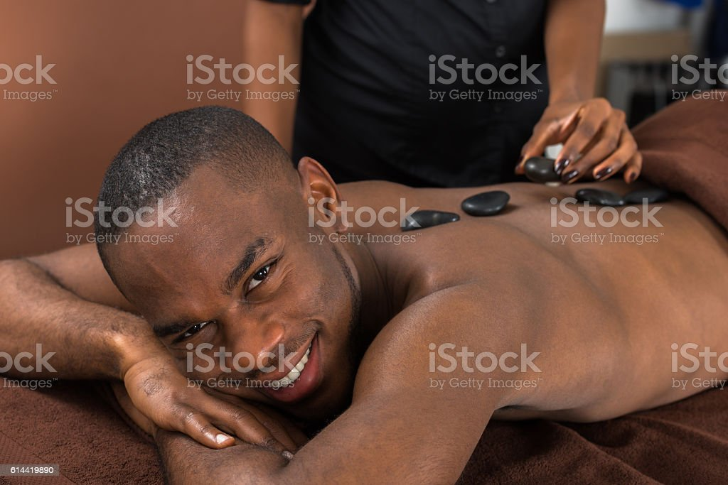 Man Getting Hot Stone Therapy stock photo
