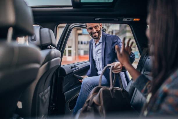 hombre entrando en el asiento trasero de un coche - uso compartido del coche fotografías e imágenes de stock