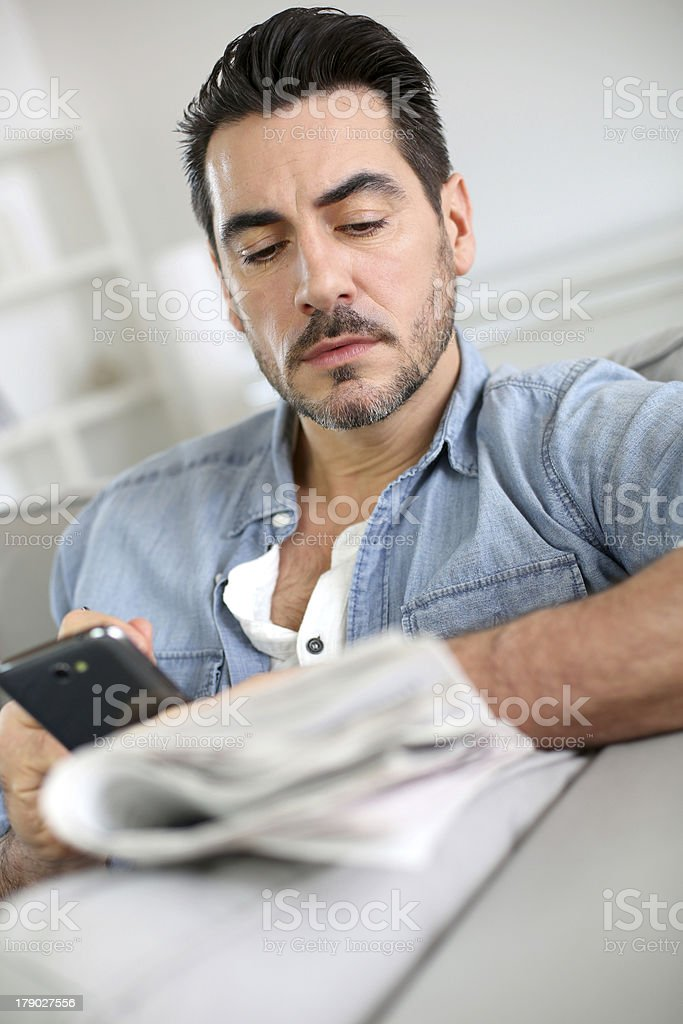 Man getting information from newspaper and smartphone royalty-free stock photo