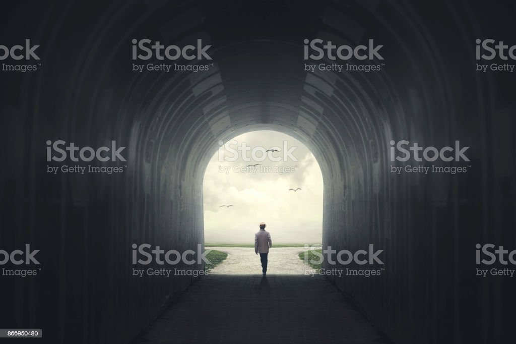 Man getting out from a dark tunnel stock photo