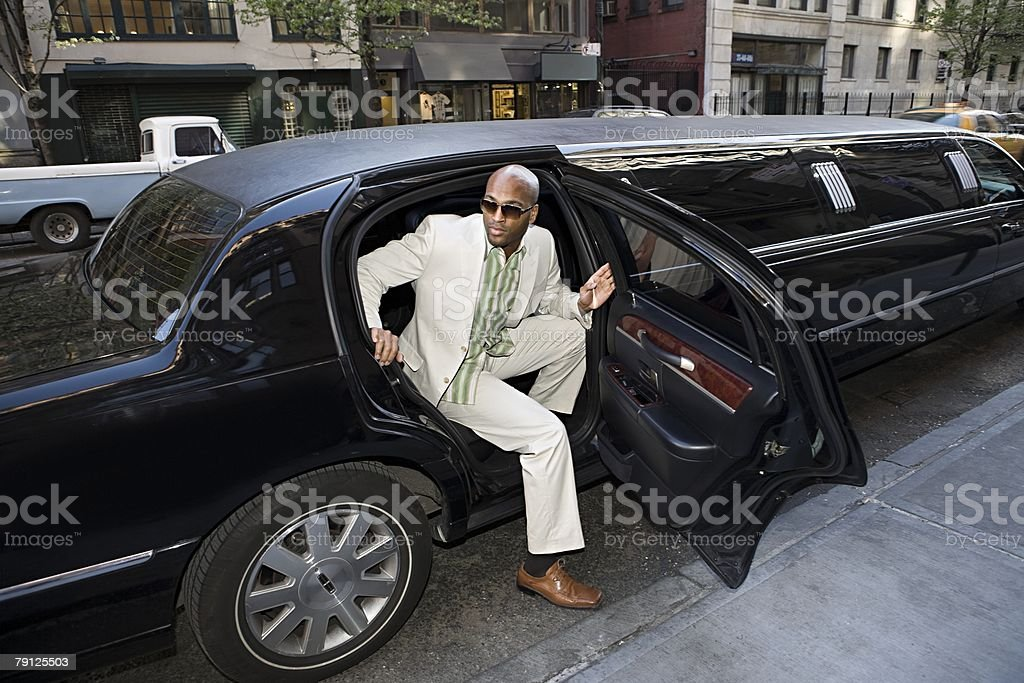 Man getting out of limousine stock photo