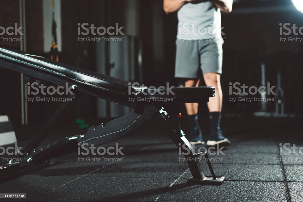 A young athlete wearing grey shorts, grey top and black shoes,...
