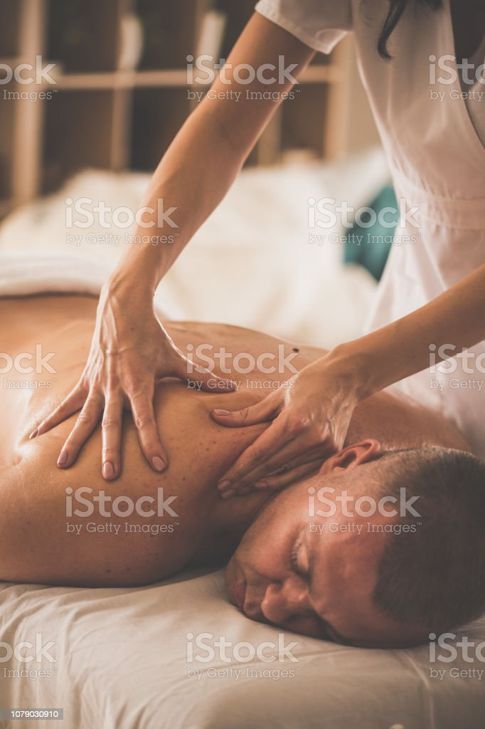 Caucasian man is lying on massage table and enjoying shoulder massage...