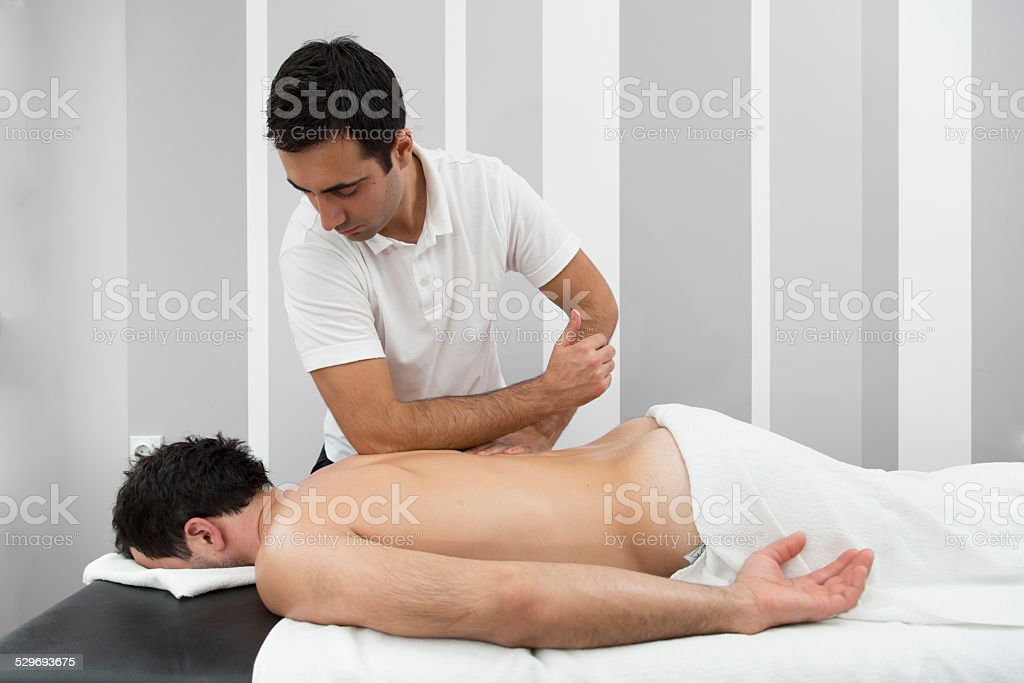 Man getting theraputic back massage with elbow stock photo