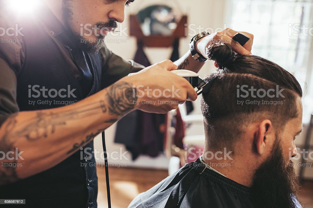Man getting trendy haircut in barber shop royalty-free stock photo