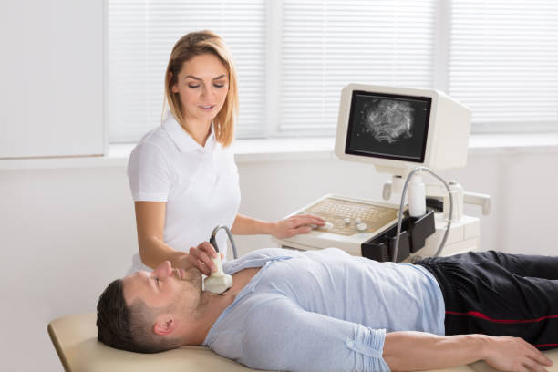 Man Getting Ultrasound Of A Thyroid From Doctor Young Man Getting Ultrasound Scan On Neck By Female Doctor In A Clinic anode stock pictures, royalty-free photos & images