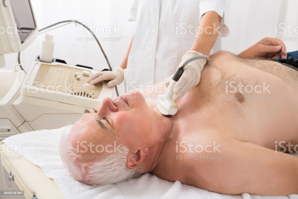 Man Getting Ultrasound Scan On Neck By Doctor stock photo