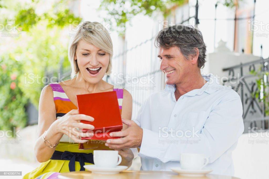 Man gifting woman at cafe stock photo