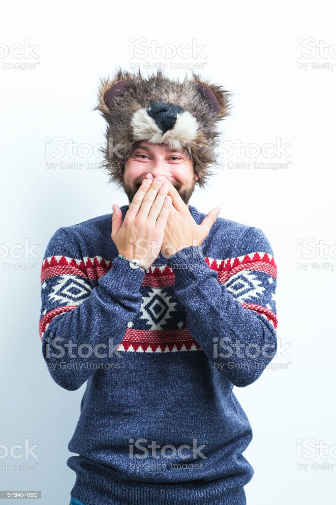 Man giggling in winter clothing Portrait of man in winter clothing covering his mouth with hand while smiling on white background Adult Stock Photo