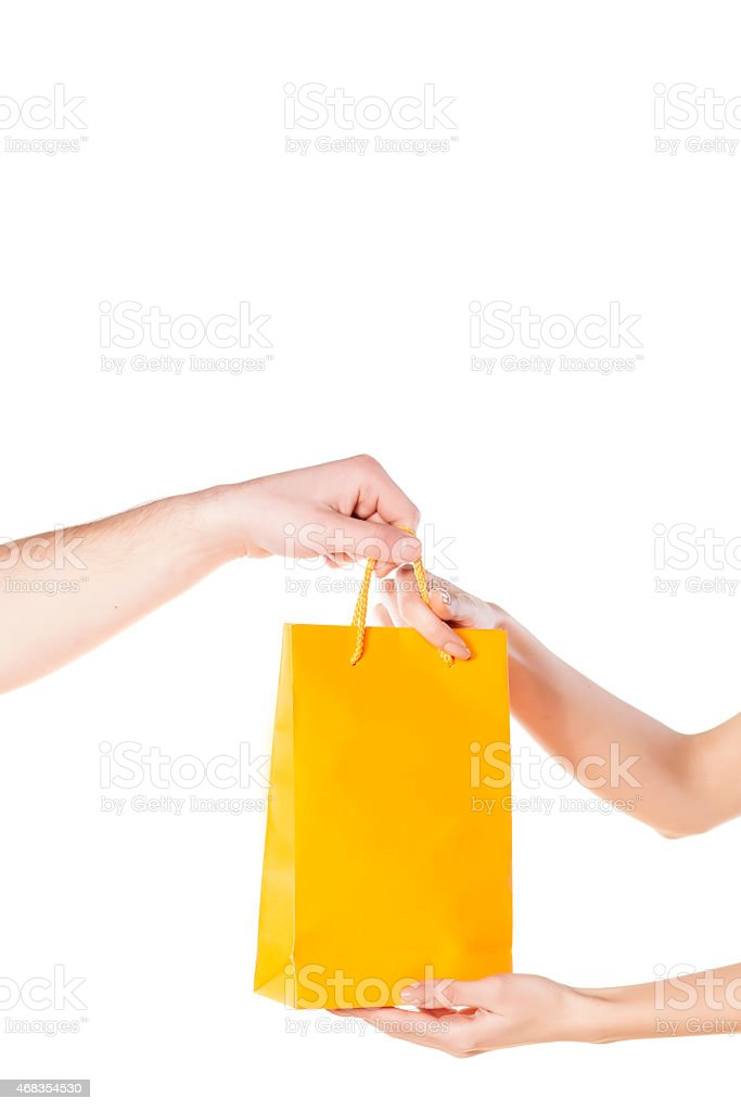 man gives a gift bag to his wife royalty-free stock photo