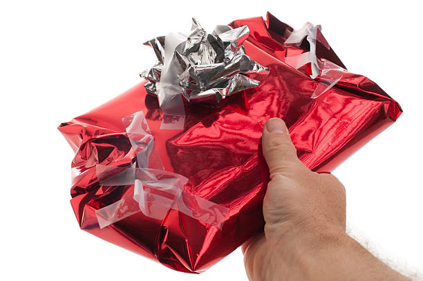Man gives badly wrapped, messy Christmas present stock photo
