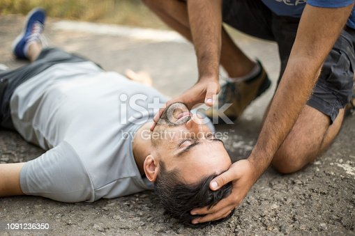 istock Man gives first aid to a person on the asphalt 1091236350