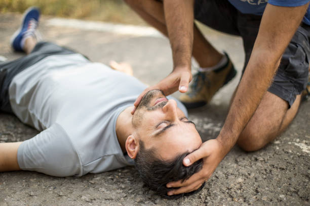 Man gives first aid to a person on the asphalt stock photo