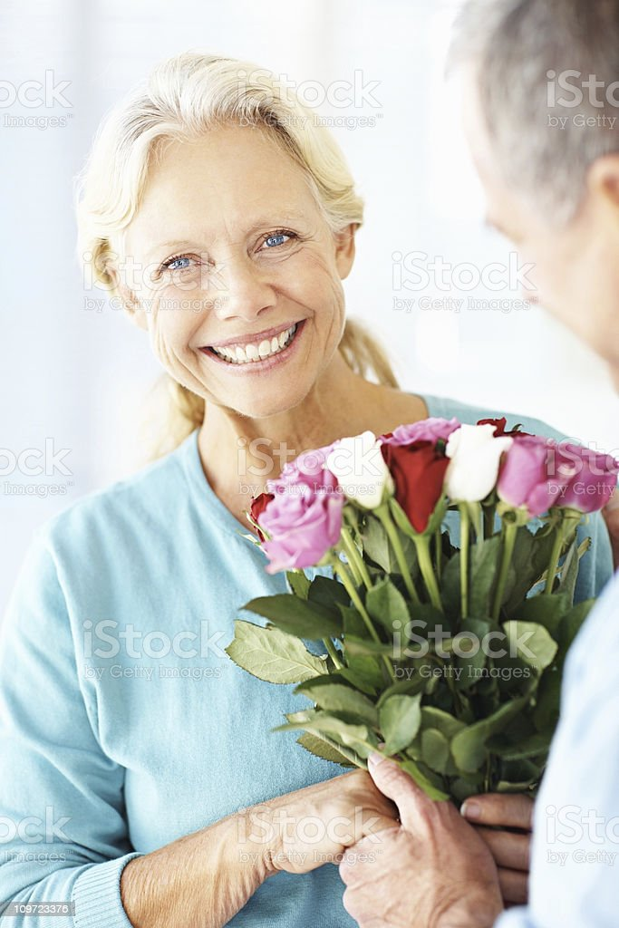 Man giving a bunch of flowers to an old woman royalty-free stock photo