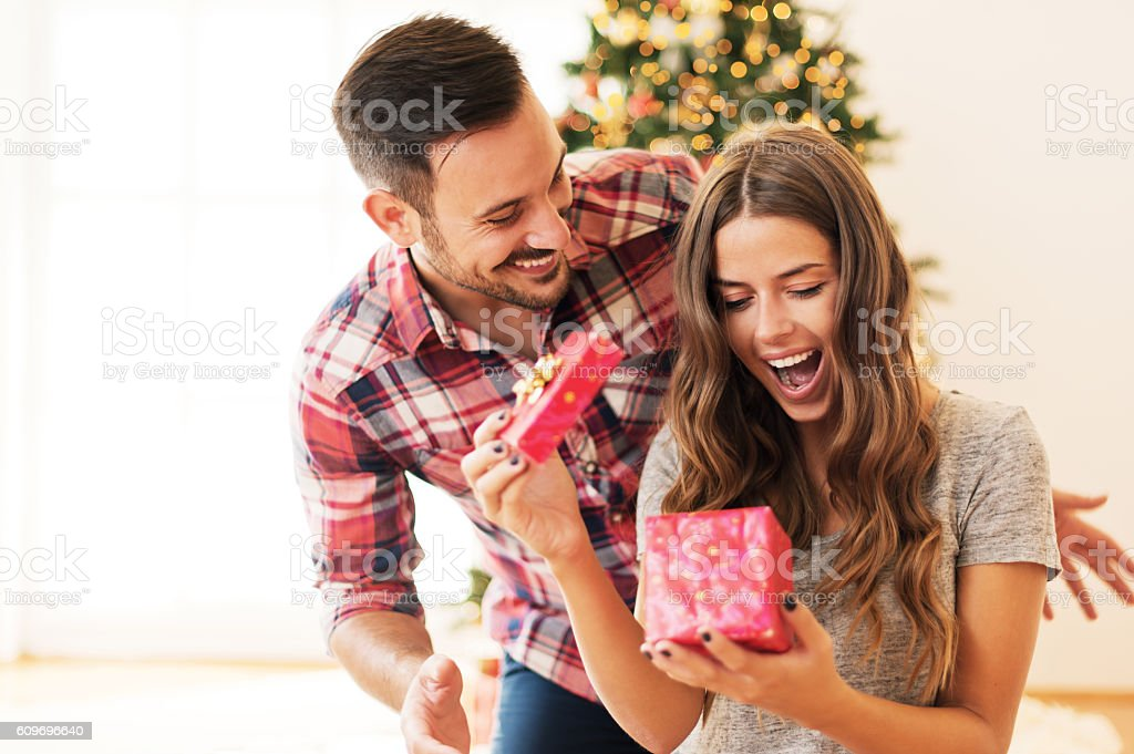 Man giving a Christmas present to his girlfriend stock photo