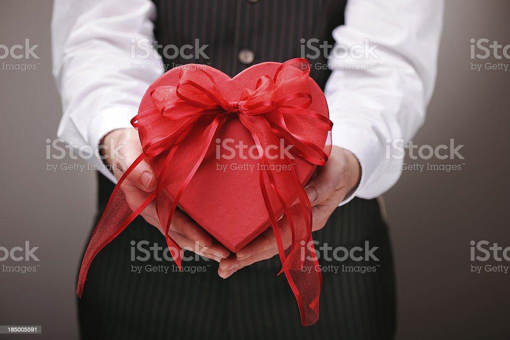 Man giving a heart shaped gift box royalty-free stock photo