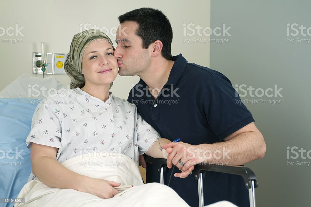 Man giving a kiss to a woman in a hospital bed stock photo