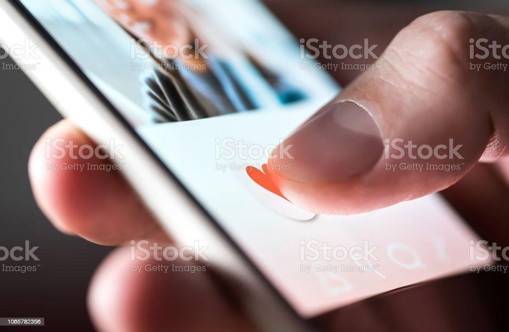소셜 미디어에 사진 처럼 주는 또는 온라인 데이트 약 손가락 밀기 심장 아이콘 스마트폰 응용 프로그램에서 화면에 슬쩍 남자. - 로열티 프리 개념 스톡 사진