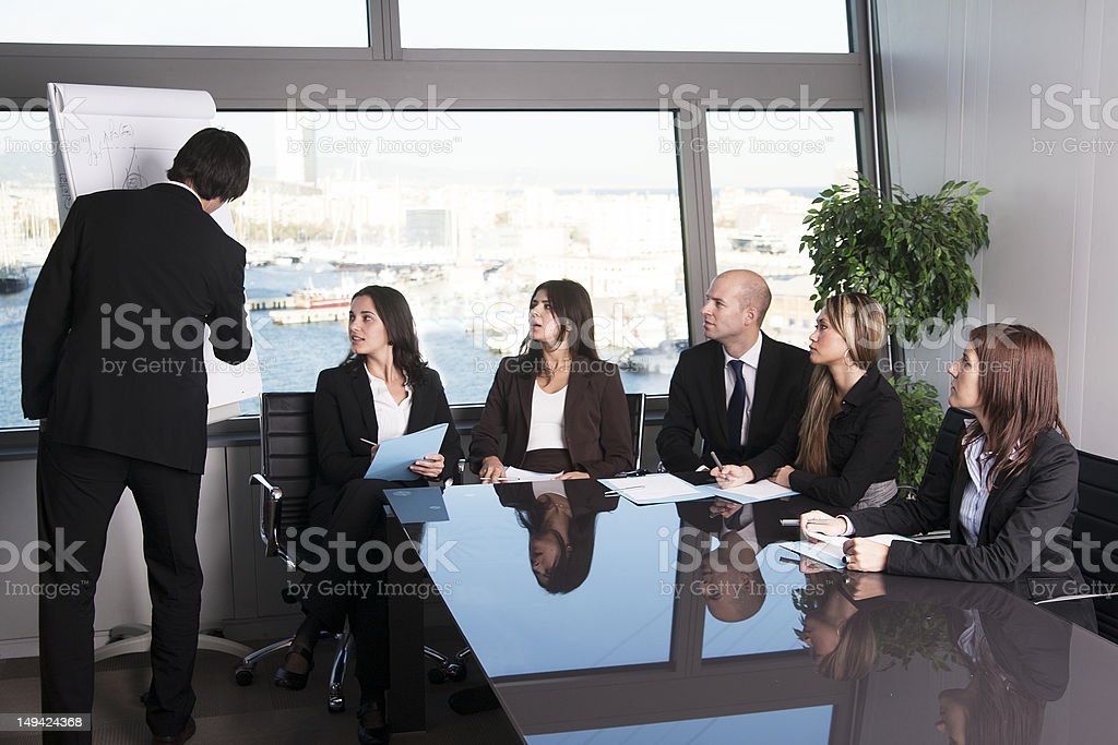 Man giving a presentation on a flip pad to colleagues royalty-free stock photo