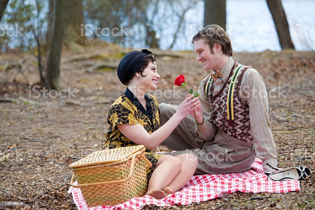 Man giving a rose to lady during picnic royalty-free stock photo