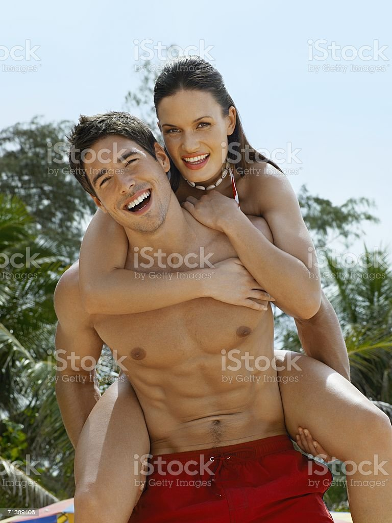 Man giving a woman a piggyback royalty-free stock photo